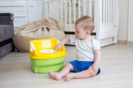 Cute 10 months old baby boy sittin on floor and playing with toilet pot