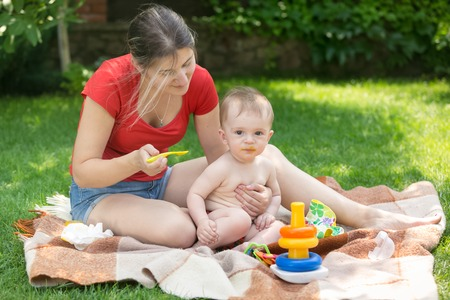 Young mother having family picnic with her baby boy and feeding him with porridge