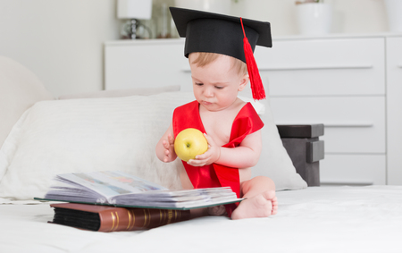 10 months old baby boy in graduation hat reading books and holding big apple