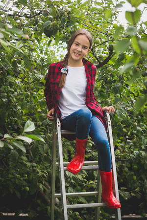 Toned photo of smiling teenage girl in red wellies sitting on top of stepladder at garden