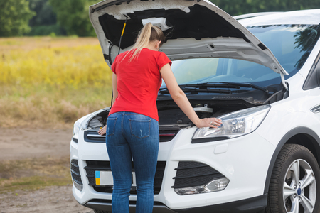 Young woman standing at broken car and looking under the hood Stock Photo