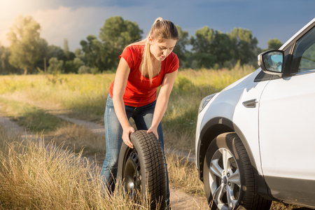 Young woman rolling spare wheel to change flate tyre on her car Stock Photo