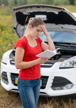 Portrait of upset young woman reading manul for her broken car in field