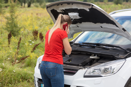 Rear view image of young woman looking under the hood of broken car and calling service Stock Photo