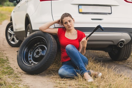 Toned image of young woman holding car wheel wrench struggling to change flat tire in field