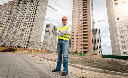Male construction engineer in hardhat standing on building site