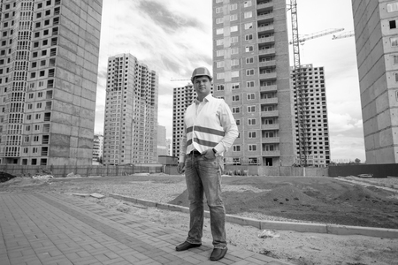 Black and white image of young builder in hardhat and vest posing on building site