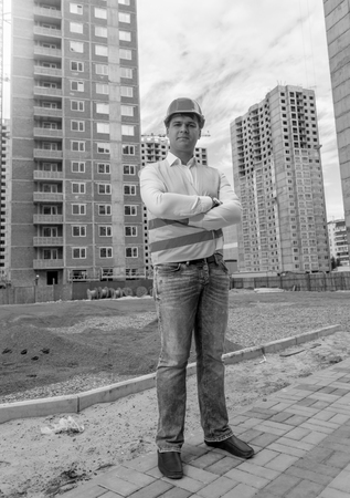 Black and white image of confident male architect standing on building site