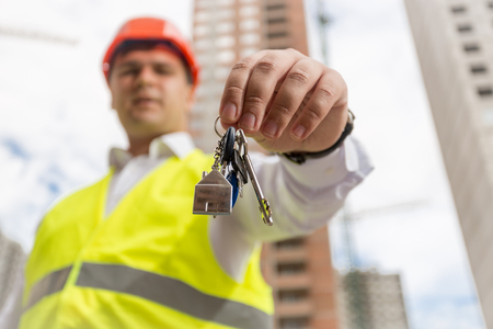 Closeup image of male businessman standing on building site and showing keys from new house