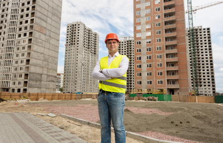 Portrait of smiling young man in safety vest and helmet posing over buildings under ocnstruction
