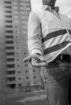 Closeup black and white image of male architect holding keys from new apartment on hand Stock Photo