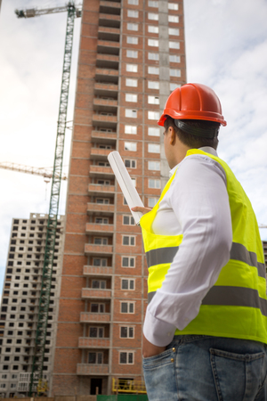Rear view image of male architect pointing at buildings under construction with roll of blueprints Stock Photo