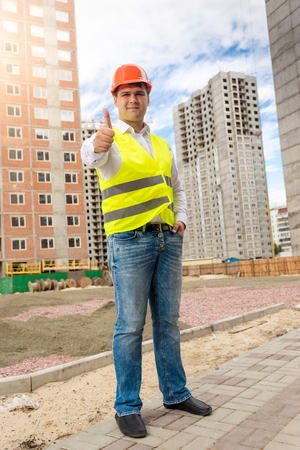 Smiling male engineer in hardhat standing on building site and showing thumbs up