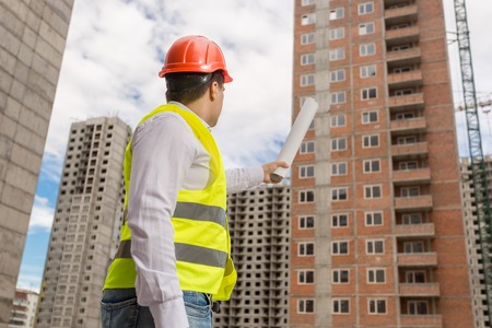 Male construction worker in hardhat holding blueprints and pointing at building under construction