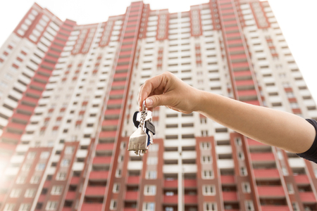 Closeup image of young woman showing keys from new apartment. Concept of real estate investment Stock Photo