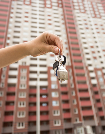 Closeup image of female hand holding keys from new apartment. New big house on the background