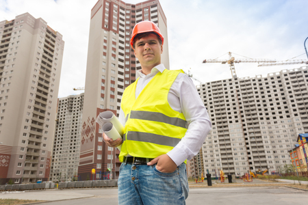 Portrait of smiling male engineer in hardhat standing with blueprints against building under construction Stock Photo