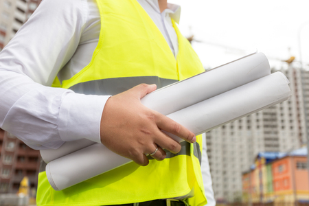 Closeup image of male architect holding blueprints of new houses