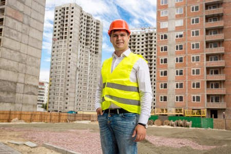 Portrait of smiling young businessman in vest and hardhat standing on building site