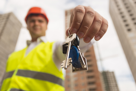 Closeup image of male construction engineer showing keys from new home in camera