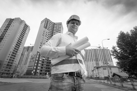 Black and white image of smiling male construction engineer in hardhat