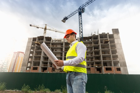 Portrait of male construction engineer standing on building site and looking at blueprints Stock Photo