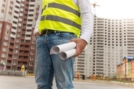 Closeup image of male architect with blueprints standing next building under construction
