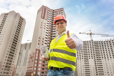Closeup portrait of smiling architect in hardhat standing on building site and hsowing thumbs up Stock Photo