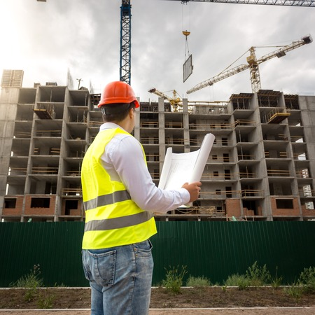 Rear view image of construction engineer controlling building new house Stock Photo