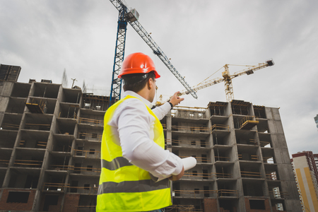 Toned image of male construction worker pointing at working cranes on building Stock Photo