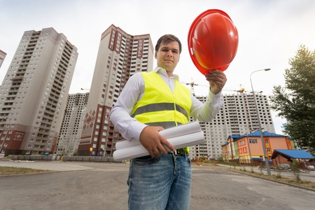 Portrait of young male architect holding red plastic hardhat on building site