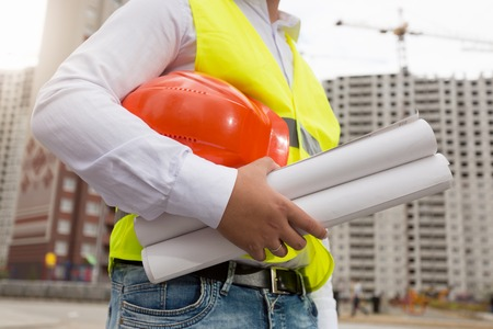 Closeup image of male engineer holding blueprints of new house and red hardhat