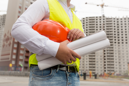 Closeup image of male builder holding blueprints and red helmet Stock Photo