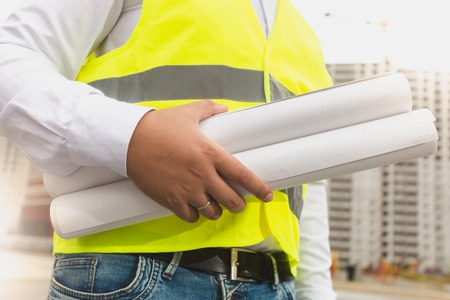 Closeup image of construction engineer holding rolled blueprints