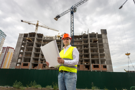 Portrait of smiling construction engineer posing with blueprints against building under construction and working cranes