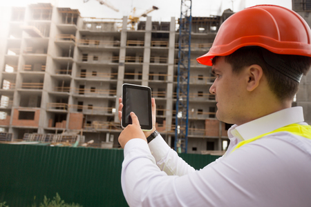 Rear view image of male building worker using digital tablet on construction site
