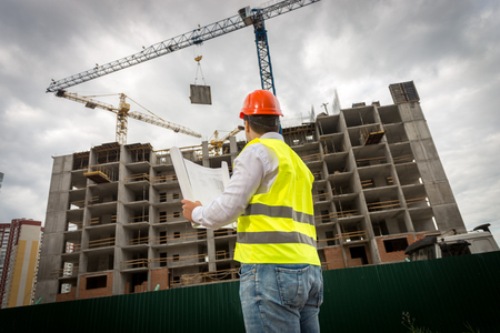 Rear view image of construction engineer in green safety vest and red hardhat controlling construction of new building