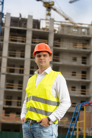 Portrait of smiling male engineer in hardhat posing against building site