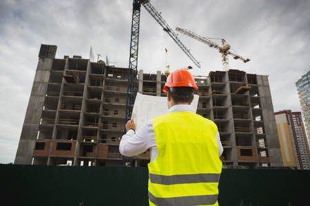 Rear view image of construction engineer checking blueprint of new building under construction