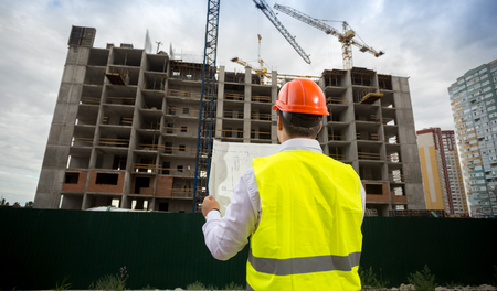 Rear view photo of male architect in hardhat standing on building site and looking on blueprints Stock Photo