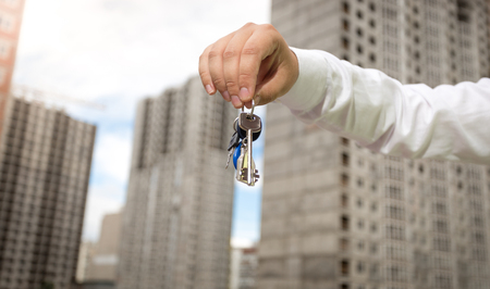 Closeup image of male hand holding keys from new house over backound of building site Stock Photo