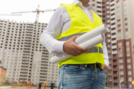 Closeup image of male architect holding blueprints of new house against building site