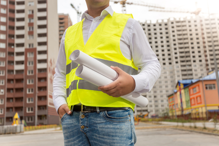 Closeup image of male architect with blueprints posing against new buildings
