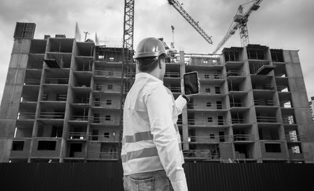 Black and white photo of male architect with digital tablet working on building site Stock Photo