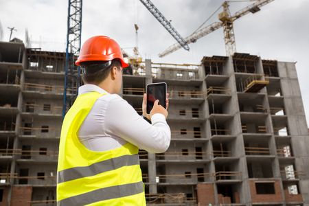 Rera view photo of businessman in safety vest and hardhat standing on building site and using digital tablet
