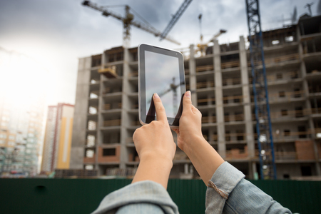 Closeup image of young woman using diigatl tablet aginst building under construction Stock Photo