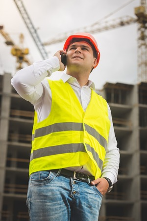Toned portrait of young male engineer talking by phone and looking at building under construction
