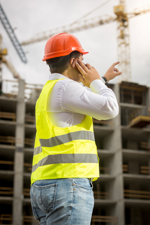 Rear view image of young businessman talking by phone on building site and pointing at building under construction