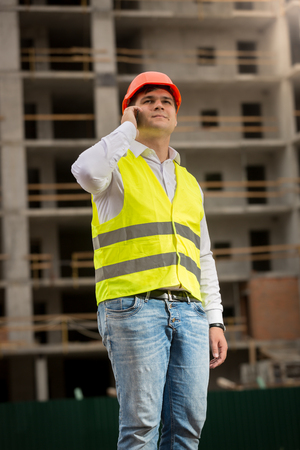 Portrait of smiling young investor in safety vest and protective helmet talking by phone on building site Stock Photo