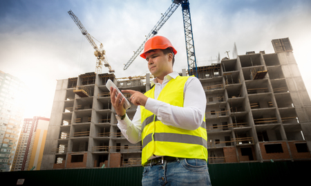 Portrait of male construction engineer standing on building site and using digital tablet